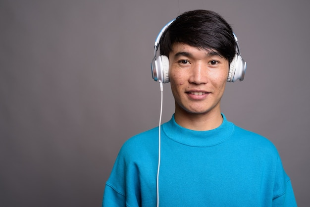 灰色の壁に対して音楽を聴いている若いアジア人男性