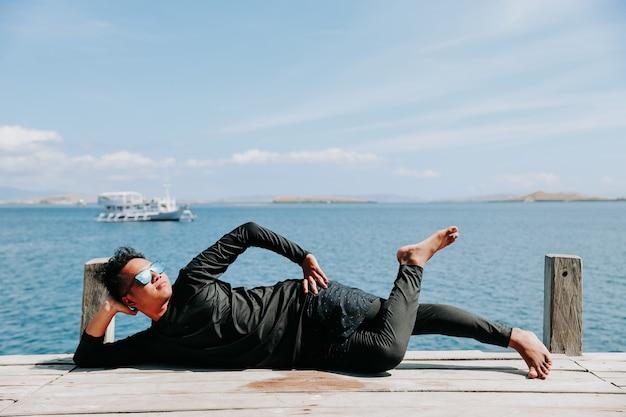 누워서 바다의 분위기를 즐기며 휴식을 취하는 젊은 아시아 남자