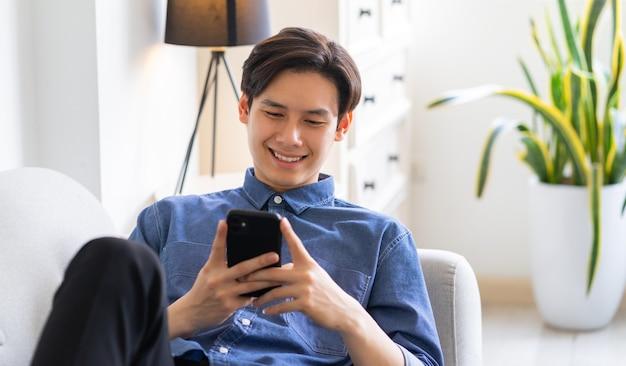 ソファに横になって電話を使用して若いアジア人男性
