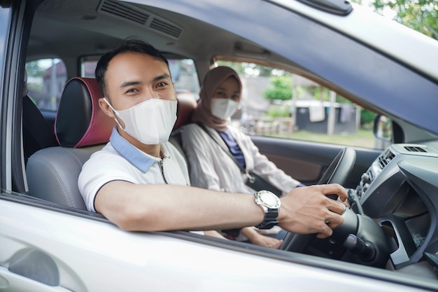 A young asian man in a mask looks at the camera while driving in a car with his partner
