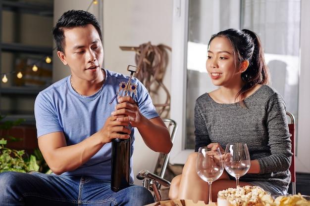 Молодой азиатский мужчина открывает вино