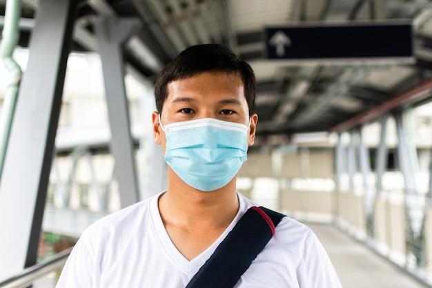 의료용 안면 마스크를 쓴 젊은 아시아 남성 승객이 하늘 기차역에 서 있다