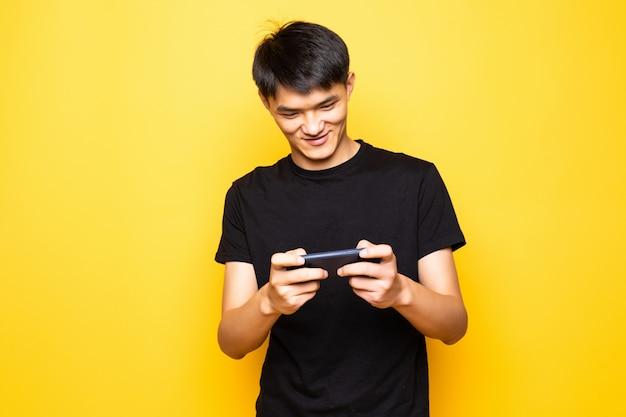 若いアジア人は黄色の壁に分離された携帯電話立ってゲームをプレイします。