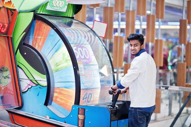Молодой азиатский человек играет на игровых автоматах колеса удачи, чтобы попытаться выиграть в лотерею с большим призом