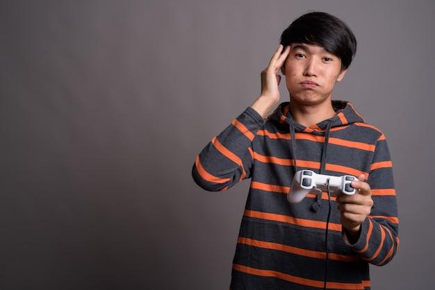 Молодой азиатский мужчина играет в игры против серой стены