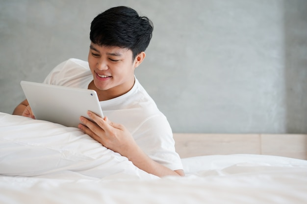 Young asian man playing tablet on bed in weekend