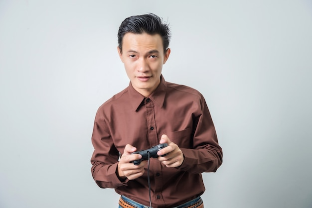 Young asian man playing video game with joystick, happy feeling.