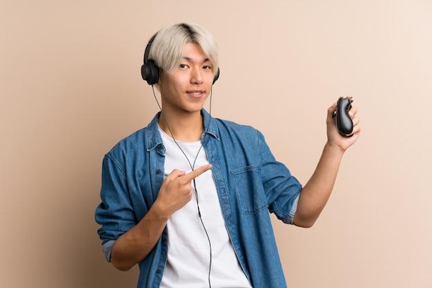 Young asian man  playing at videogames