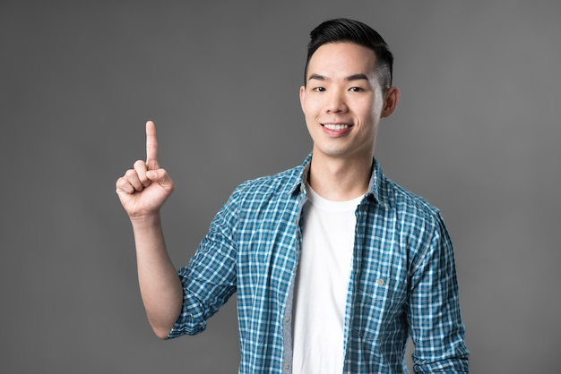 Young asian man pointing his finger up