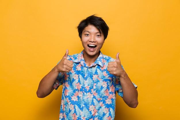 親指を立てるジェスチャーを示す黄色の空間に孤立してポーズをとる若いアジア人。