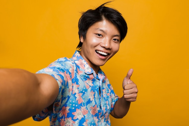 Young asian man posing isolated over yellow space take a selfie with thumbs up gesture.