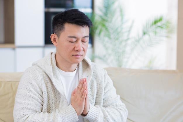 一人で家で祈る若いアジア人