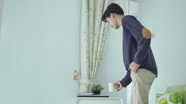 仕事の後にテーブルに眼鏡をかける若いアジア人男性