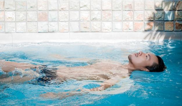 若いアジア人男性がリラックスしてプールでスパ。