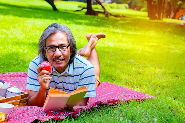 Young asian man relax time in park. in the morning he is reading book with red apply
