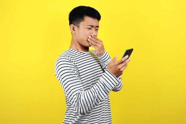 Молодой азиатский мужчина увидел невероятное уведомление на своем телефоне, изолированном на желтом фоне