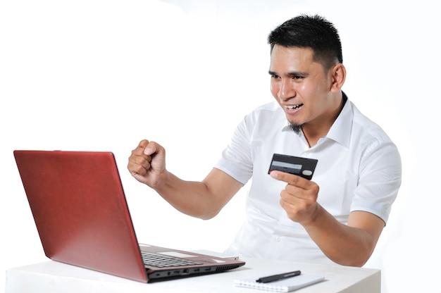 それを支払うためにデビットカードを使用してオンラインショッピング、白い背景で隔離の若いアジア人男性