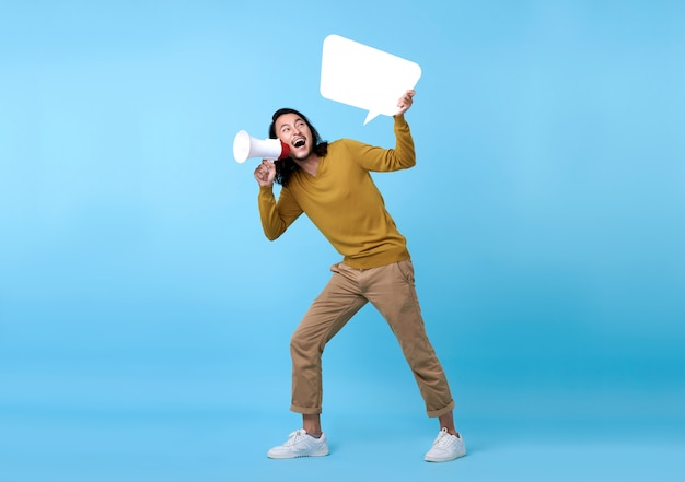 Young asian man shouting into megaphone and holding speech bubble isolated on blue space.
