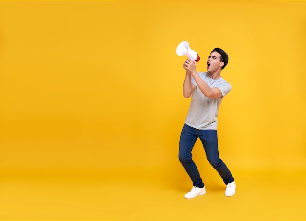 Young asian man shouting into megaphone making announcement in on yellow.