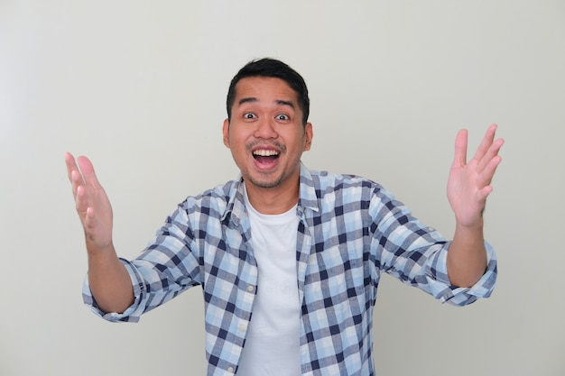 Молодой азиатский мужчина показывает возбужденное выражение лица, пытаясь что-то получить