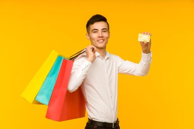 Молодой азиатский мужчина показывает свою хозяйственную сумку и кредитную карту на желтом фоне