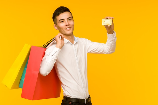 Молодой азиатский мужчина показывает свою хозяйственную сумку и кредитную карту на желтом пространстве