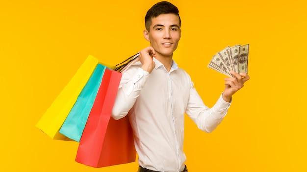 노란색 배경에 그의 쇼핑백과 돈을 보여주는 젊은 아시아 남자