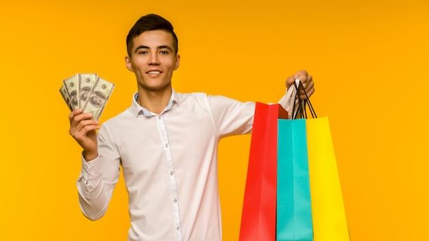 Молодой азиатский мужчина показывает свою сумку и деньги на желтом фоне