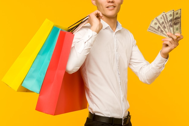 Young asian man showing his shopping bag and money on yellow background