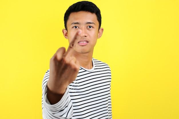 黄色の背景に分離された、中指があなたに悪い表現、挑発、失礼な態度をファックしていることを示す若いアジア人男性