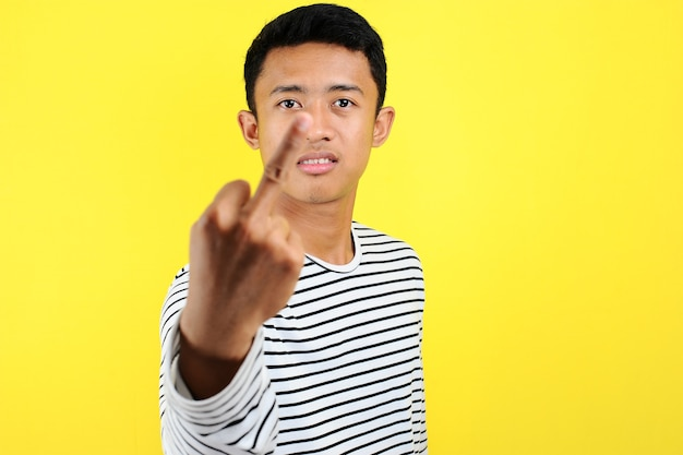 Young asian man showing middle finger doing fuck you bad expression, provocation and rude attitude, isolated on yellow background