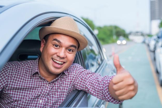 車に座っている間親指を現して若いアジア人