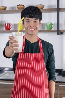 A young asian man shows smoothie lemonade.