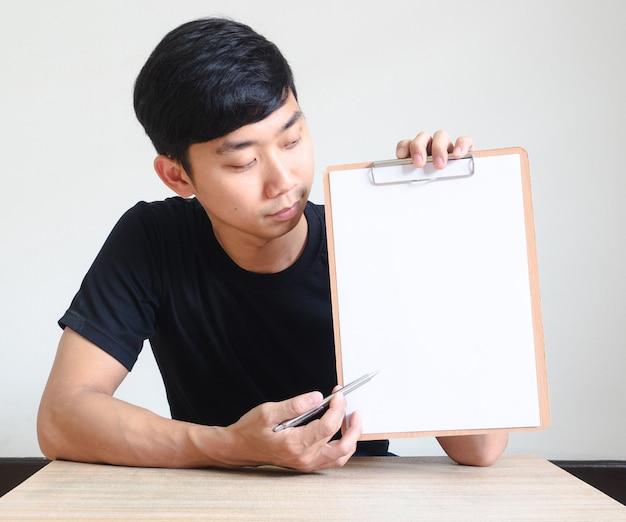 젊은 아시아 남자는 책상에 앉아 빈 문서비즈니스 개념에서 클립보드가 펜을 가리킵니다.