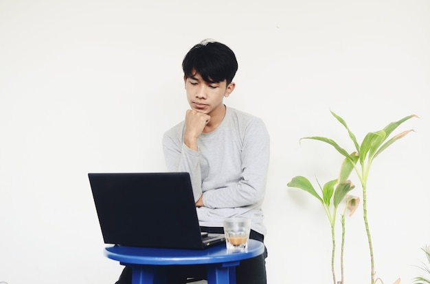 暗い顔でラップトップに座っている若いアジア人