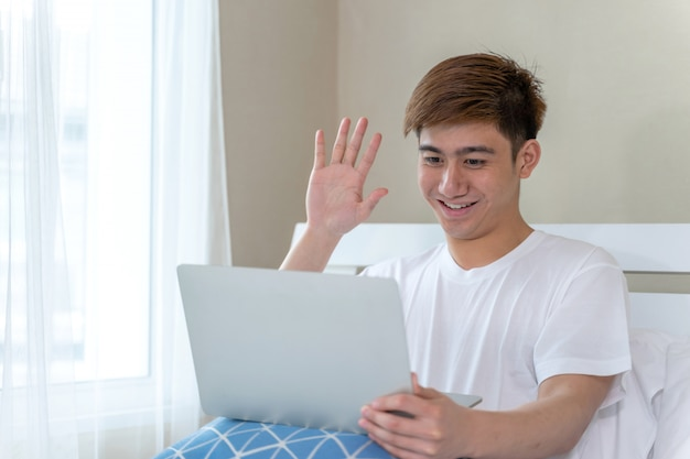 Young asian man sitting on bed, using laptop computer fill happy at home
