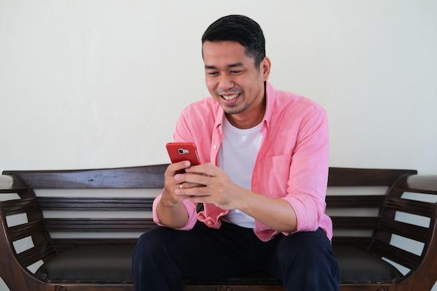 소파에 앉아 휴대폰을 사용하여 문자 메시지를 보내는 젊은 아시아 남자