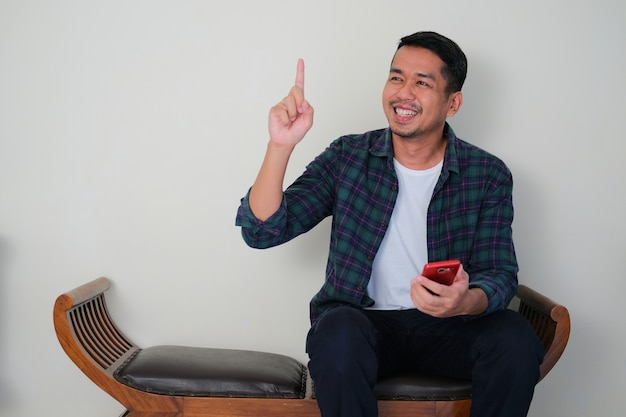 소파에 앉아 휴대전화를 들고 한 손가락을 들어올리는 젊은 아시아 남자