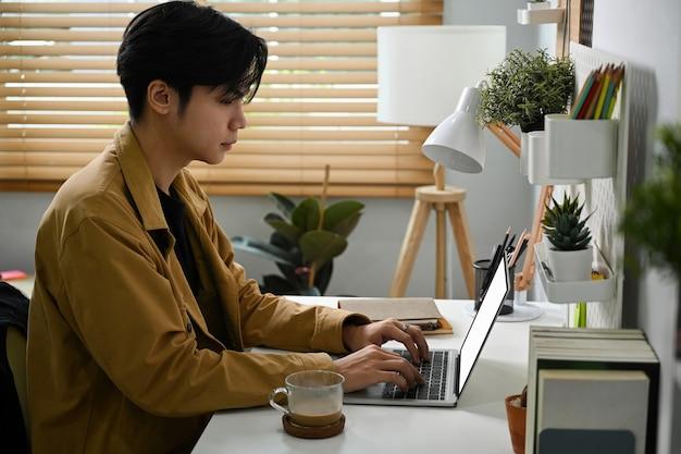 Молодой азиатский человек сидит в домашнем офисе и работает с портативным компьютером.