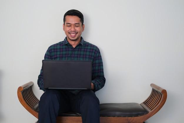 그의 노트북으로 작업하는 동안 나무 소파에 앉아 젊은 아시아 남자