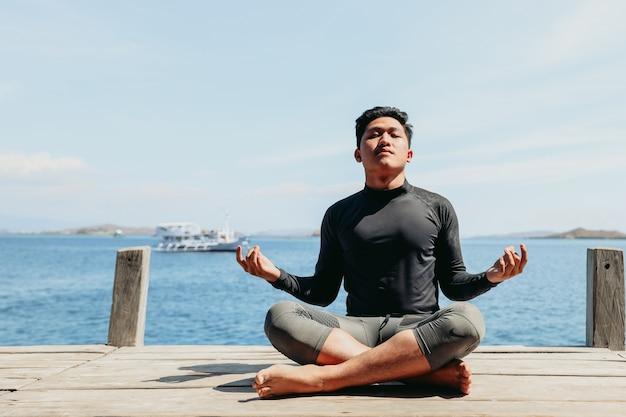 ヨガの位置に座って、海の背景で瞑想アジアの若い男
