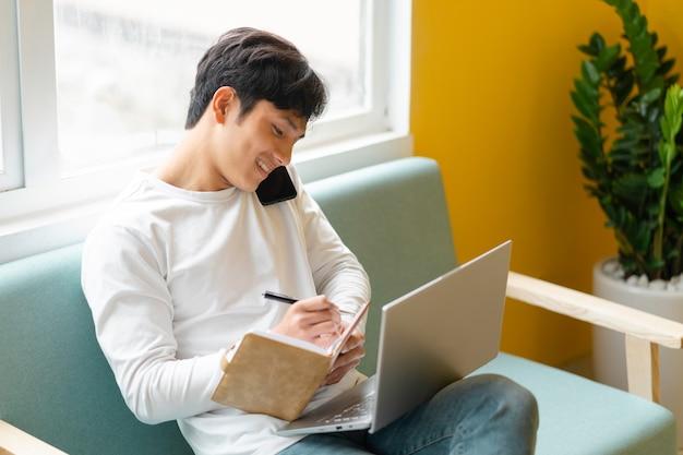 집에서 일하고 앉아 젊은 아시아 남자