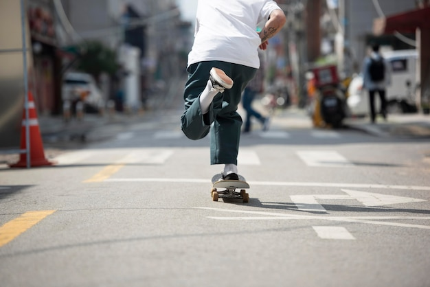 Young asian man skateboarding in the city outdoors