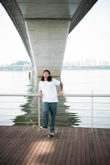 街の屋外でスケートボードをする若いアジア人男性