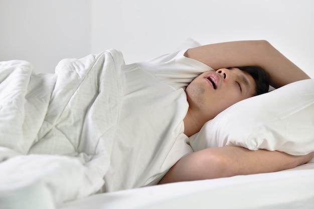 ベッドに横たわって大声で寝ていびきをかくアジアの若い男