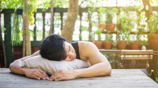 Young asian man sleeping in a garden.