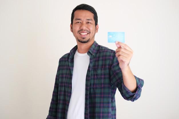 彼の空白のクレジットカードを見せながら自信を持って笑っている若いアジア人男性