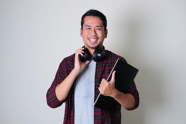 Молодой азиатский мужчина уверенно улыбается, нося гарнитуру на шее и держа портативный компьютер
