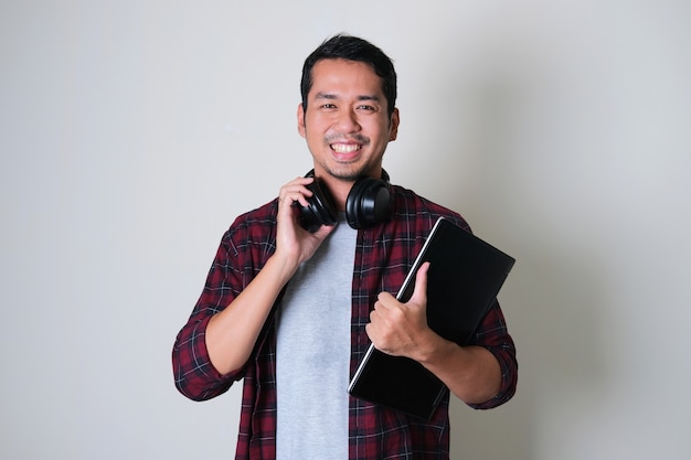 Young asian man smiling confident while wearing headset in neck and holding laptop computer