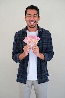 젊은 아시아 남자가 그의 지폐를 보여주면서 흥분해서 웃고 있다